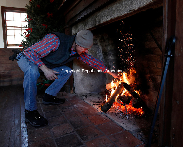 Roxbury, CT- 27 December 2013-122813CM08-   COUNTRY LIFE ONLY PLEASE---  Tom Yost of Roxbury adds wood to a fire inside during an open house at the Good Hill School house in Roxbury on Saturday afternoon.    Christopher Massa Republican-American