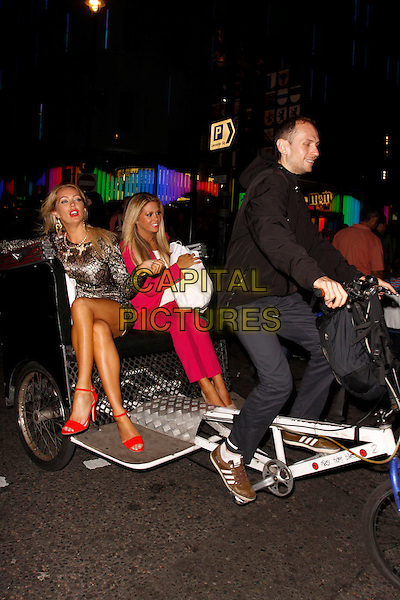 Aisleyne Horgan-Wallace and Bianca Gascoigne<br /> The Bloggers Love Collection fashion show, The Penthouse, London, England. August 22nd, 2013<br /> full length pink suit blazer white top lace dress  black goody bag sitting legs crossed rickshaw <br /> CAP/AH<br /> &copy;Adam Houghton/Capital Pictures