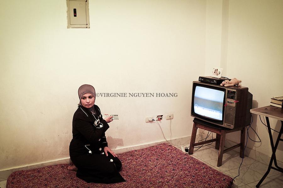 EGYPT, 6 of October city: Maha is watching some turkish programs on tv while keeping an eyes on the children. <br /> <br /> Egypte: ville du 6 octobre: Maha regarde des programmes turques &agrave; la TV tout en gardant un oeil sur les enfants.