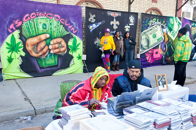 People pose for a photo in front of a painted mural on canvas, set up near the interstate overpass on Claiborne Avenue in downtown New Orleans on Mardi Gras day, February 16, 2010.  <br /> <br /> Many backdrops with many messages are set up all throughout the area by entrepreneuring photographers who instantly print the photos for their customers.  The area around the intersection of Claiborne and Orleans Avenues has long been a meeting place for Mardi Gras Indians and the African American community in general on Mardi Gras Day.