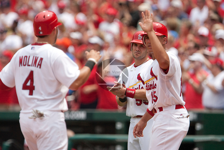 July 4, 2010         St. Louis Cardinals catcher Yadier Molina (4) crosses home plate and is congratulated by teammates John Jay (15, right) and Skip Schumaker (55, center).   The trio of Cardinals players all scored in the third inning after St. Louis Cardinals starting pitcher Adam Wainwright doubled to right centerfield.  Wainwright, Molina, Albert Pujols, Chris Carpenter, and Matt Holliday were all selected to play in the All-Star Game.  The St. Louis Cardinals defeated the Milwaukee Brewers 7-1 in the final game of a four-game homestand at Busch Stadium in downtown St. Louis, MO on Sunday July 4, 2010.