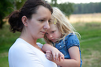 Polish mom having a somber moment holding her daughter age 32 and 4. Zawady Central Poland