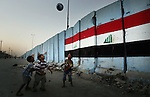 BAGHDAD, IRAQ – AUGUST 06: Iraqi children paly next to a painted  cement block wall on August 6, 2008 in the Shiite district of Sadr city east of Baghdad, Iraq. The wall was constructed by both U.S and Iraqi army for security reasons. (Photo by Wathiq Khuzaie /Getty Images)....