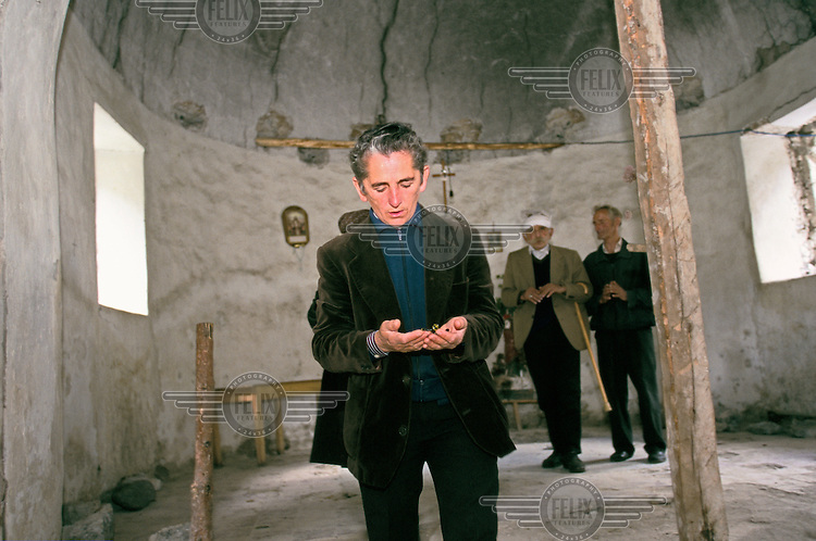 Pashke Sokol Ndocaj prays in the crumbling local church. Since the death of her father and brothers, Pashke has lived as a man in the ancient traditions of Avowed Virgins of Albania, where women renounce their former sex and 'become' men to head the family.