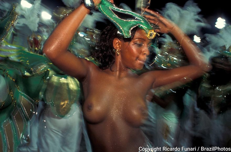 Beautiful young black nude woman dances samba in front of drummers at Samba schools parade, Rio de Janeiro carnival, Brazil.