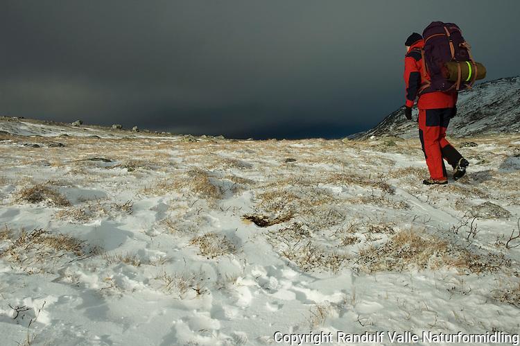 Jente går i snø mot mørk himmel. ---- Girl hiking in snow.