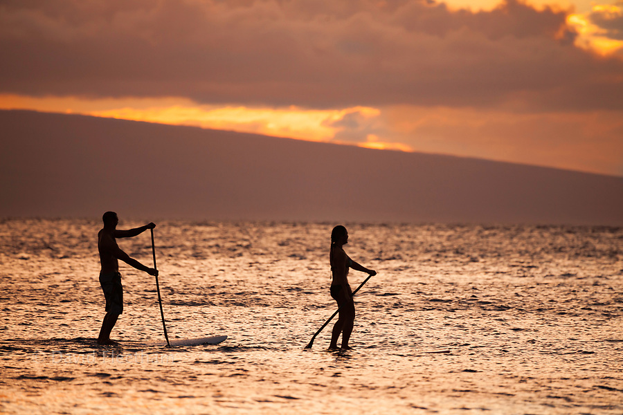 A fit male and female on stand up paddle boards enjoy a gorgeous sunset with the island of Lanai in the background off Maui, Hawaii, USA.