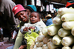 A mother and her baby selling salad at the Analakely market in Antananarivo in Madagascar