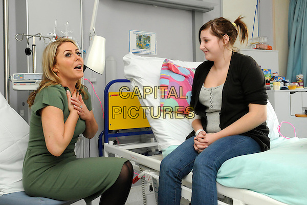 PATSY KENSIT.Patsy Kensit pays a visit to the wards of Great Ormond Street Hospital, London, UK..December 13th, 2010.half length green dress patient kid child sitting bed hand side mouth open sick ill .CAP/FIN.©Steve Finn/Capital Pictures.