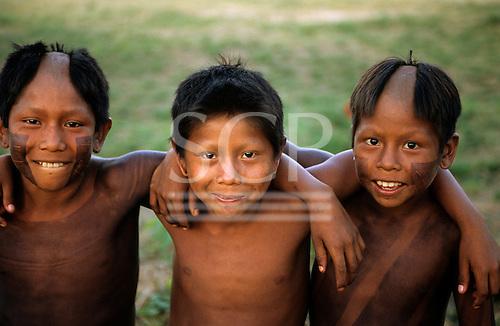Bacaja village, Amazon, Brazil. Three boys, smiling, by the village football pitch; Xicrin tribe.
