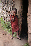 Africa, Kenya, Maasai Mara. A young child stands at the door of his boma, a traditional Maasai home.