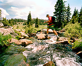 USA, Wyoming, man with backpack crossing stream, Yellowstone National Park