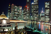 Singapore. Downtown. Town center. View at night on the City hall, Boat Quay and the Central Business District. Giant high-rise buildings. A boat sails on the Singapore river.  © 2001 Didier Ruef