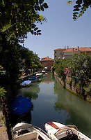 Narrow canal on the island of Lido, showing moored boats and residential Venice, Italy,May 2007.