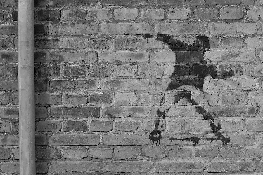 Spray-art on wall. Man throwing something. Indicating violence, disturbance of peace, protest.