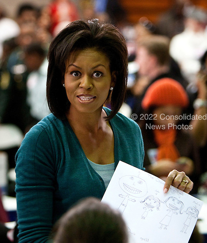 Washington, DC - January 19, 2009 -- Michelle Obama holds up a picture of her family drawn by a girl at Calvin Coolidge High School where students, military families, and volunteer service groups are working on various projects supporting the troops  in Washington, D.C., U.S., Monday, January 19, 2009.    .Credit: Joshua Roberts - Pool via CNP