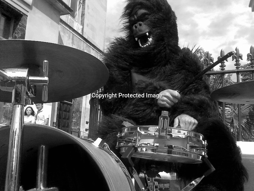 England, Eastbourne. Monkey playing drums with Asian tourists