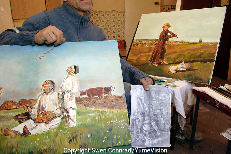 Chechen man with his paintings and drawings in the URiC Wola Refugee Centre in Poland..The former director of the  House of Culture of Grozny, Chechnya, he has left his wife and 3 other children to save the life of his 14 years old son who was kidnapped several times and tortured by the Russian Security Service to make him admit that he has weapon and forcing him to render it. No one in their family have ever had any weapon....Since they came to Poland 1 year ago he has no news from his wife and children whove left in Chechnya hiding in the family house in the mountains..He makes copies of paintings of polish artists to sell them and earn a bit of money for oil and  paintbrushes. I do not have have enough money for my own art, he says..-For security reason, the face of the adult asylum seeker have been evicted of the photography..-For security reason, the names of the adult asylum seeker have been change. .-Article 9 of the Act of 13 June 2003 on grating protection on the Polish territory (Journal of Laws, No 128, it. 1176) personal data of refugees are an object of particular protection..-Cases where publication of a picture or name of asylum seeker had dramatic consequences for this persons and is family back in Chechnya. .Please have safety of those people in mind. Thank you.