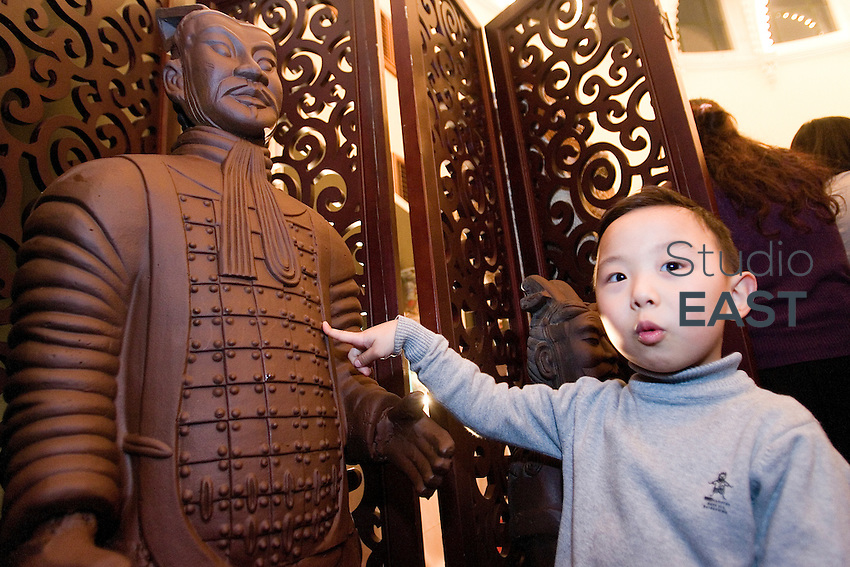 A little boy points at a Terracotta warrior made of chocolate, in 'Salon du chocolat' in Shanghai, China, on January 20, 2010. The first edition of 'Salon du chocolat' chocolate fair in Shanghai is held January 21-23, 2010. Photo by Lucas Schifres/Pictobank