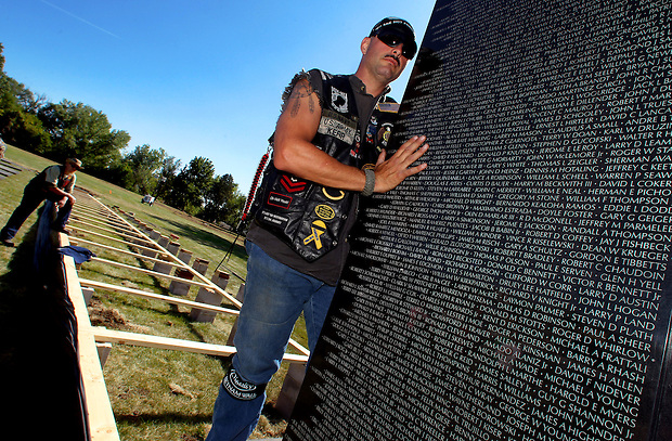 Vietnam-era veteran Jeff Kerr of Ankeny  holds a panel bearing the names of those killed or missing in the Vietnam War during assembly of The Dignity Memorial Vietnam Experience Wednesday at Resthaven Cemetery in West Des Moines.  The display, a traveling, three-quarter-scale replica of the Vietnam Veterans Memorial in Washington, D.C., will be open to school children on Thursday and to the public at  from Friday to Sunday. The faux-granite replica is 240 feet long, eight feet high and contains the names of more than 58,000 Americans who died or are missing in Vietnam. More than 30,000 people are expected to see the display while it is in West Des Moines.  (Christopher Gannon/The Des Moines Register)