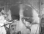 North East PA:  Baker putting bread into an oven.