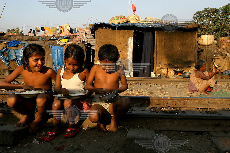 Three children, sitting on some railway tracks running through the Dhaka slum, where they live, eat food from tin plates.