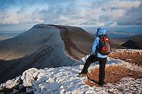 Single female hiker enjoys winter view of Pen Y Fan from Corn Du, Brecon Beacons national park, Wales