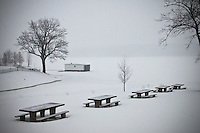Snow covers picnic tables along a frozen lake in winter. Boathouse sits frozen in lake.