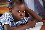 A girl studies in a temporary school classroom in Jean-Rabel in northwestern Haiti. His elementary school was heavily damaged during Hurricane Matthew in 2016, but Church World Service, a member of the ACT Alliance, is helping the community repair the school.
