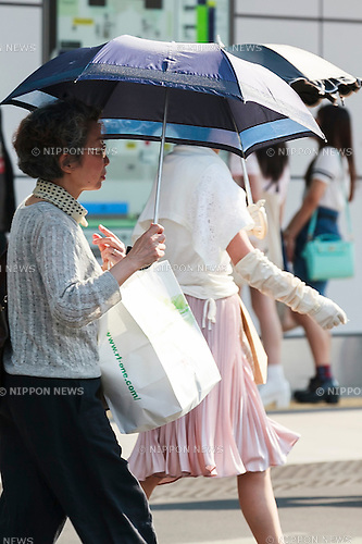 Pedestrians hold parasols on the hottest day so far of 2016 in downtown Tokyo on May 23, 2016. Tokyo registered its hottest day of the year so far with temperatures hitting 31C degrees in Shinjuku at 3pm. (Photo by Rodrigo Reyes Marin/AFLO)