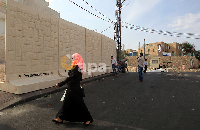 A Palestinian woman walks in front of a newly erected separation wall in Jerusalem's neighborhood of Jabal al-Mokaber on October 19, 2015. Israeli police began erecting a wall in east Jerusalem to protect a Jewish neighbourhood subject to firebomb and stone attacks launched from an adjacent Palestinian village. Photo by Mahfouz Abu Turk