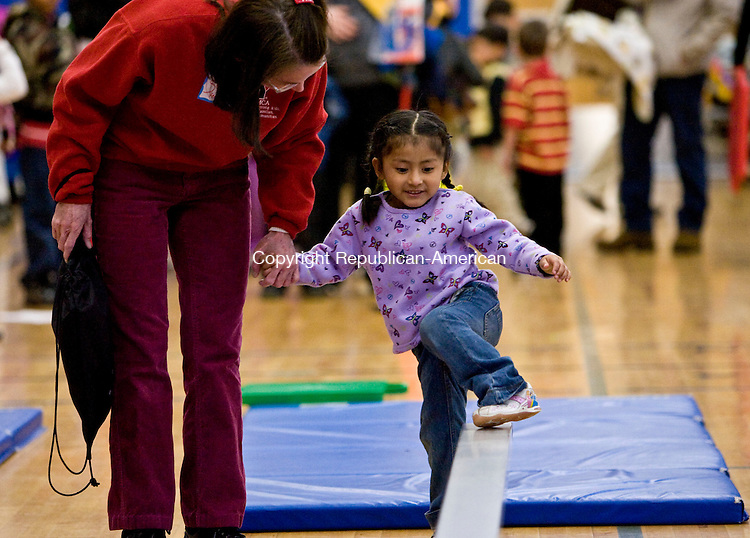 TORRINGTON, CT - 13 MARCH 2010 -031310JT04-<br /> Suzanne Remington-Fox helps Melissa Duman, 3, across a balance beam during the Kindergarten Readiness Fair sponsored by the Torrington Early Childhood Collaborative in cooperation with the school district at Torringford Elementary School. <br /> Josalee Thrift Republican-American