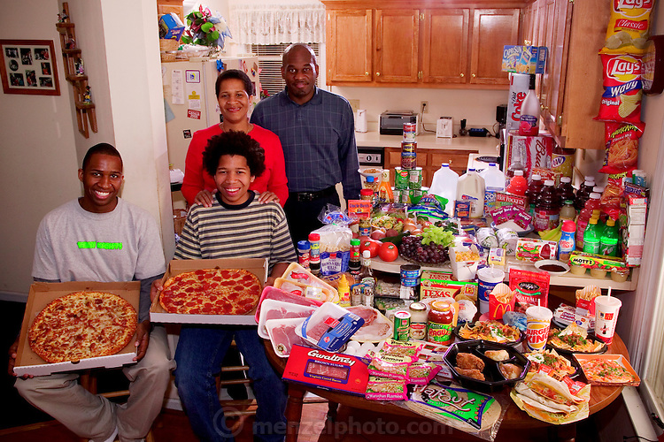 (MODEL RELEASED IMAGE). The Revis family in the kitchen of their home in suburban Raleigh, North Carolina, with a week's worth of food. Ronald Revis, and Rosemary Revis, stand behind Rosemary's sons from her first marriage, Brandon Demery, (left), and Tyrone Demery. The Revis family is one of the thirty families featured in the book Hungry Planet: What the World Eats (p. 266).