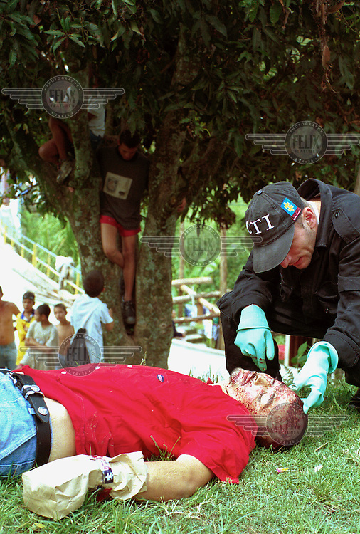 ©Paul Smith/Panos Pictures..COLOMBIA: MedellÌn..A member of the CTI (Technical Investigation Corps) inspects the body of a murder victim on the outskirts of the city.