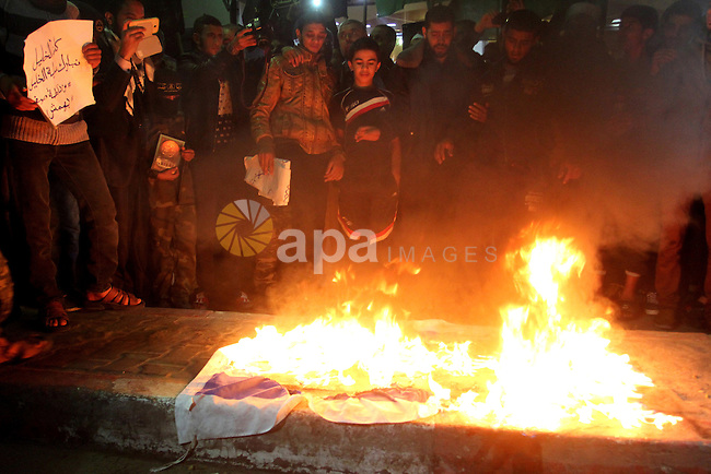 Palestinian protesters stand burn an Israeli flag during a protest to support the third Palestinian uprising, in Rafah in the southern Gaza Strip November 13, 2015. The current wave of violence erupted in mid-September, fueled by rumors that Israel was trying to increase Jewish presence in Jerusalem then quickly spread across Israel, the West Bank and the Gaza Strip. Photo by Abed Rahim Khatib