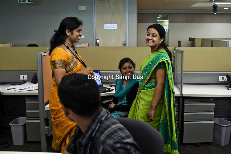 Ernst & Young employees share a lighter moment at the Ernst & Young Global Shared Services office in Bangalore, Karnataka, India. Ernst & Young has 49% women working for them in the India office. Photo: Sanjit Das