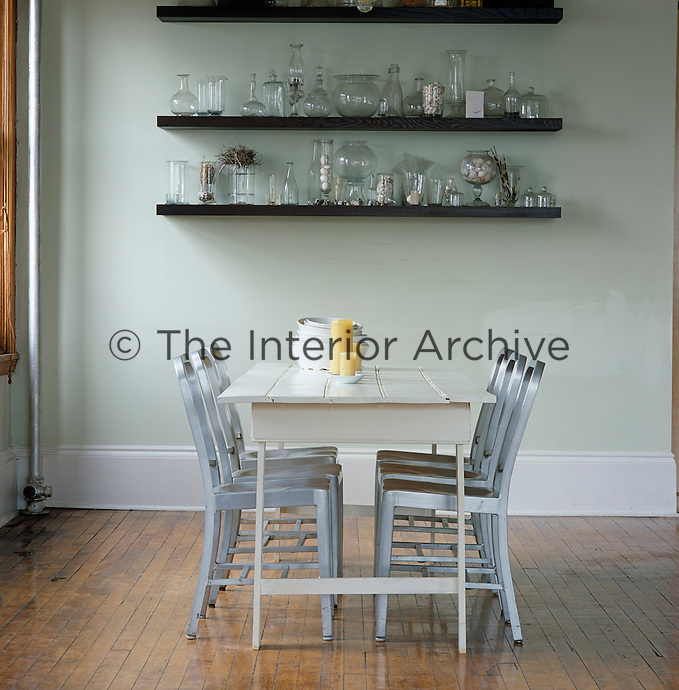 Open shelving with a display of collectable glassware helps to define the dining area in this open plan loft space