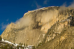 Cloud forming against the huge granite rock cliff face of Half Dome at sunset, Yosemite National Park, California