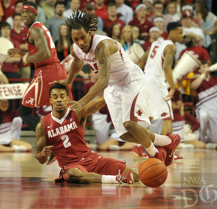 NWA Democrat-Gazette/Michael Woods --01/06/2015--w@NWAMICHAELW... University of Arkansas guard Michael Qualls steals the ball from Alabama's Ricky Tarrant as he converts the turnover to an easy dunk during the first half of Thursday nights game at Bud Walton Arena in Fayetteville.