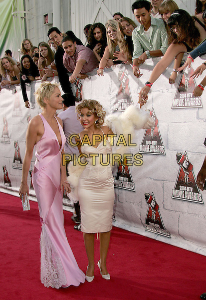 SHARON STONE & CHRISTINA AGUILERA.at the 2004 MTV Movie Awards held at The Sony Picture Studios in Culver City, .California,.6th June 2004..full length full-length furry fluffy wrap shawl long pink dress walking greeting crowd.*UK sales only*.www.capitalpictures.com.sales@capitalpictures.com.©Capital Pictures