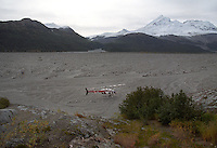 Researchers from the Alaska Volcano Observatory and their helicopter are dwarfed in 1999 as they check a location in the Drift River flood plain. Mount Redoubt's summit cone rises in the distance. During eruptions, pyroclastic flows cause flooding in the river. The flooding threatens Chevron's Drift River oil facility.