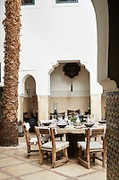 A round stone table is laid for an alfresco lunch on the courtyard patio