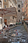 Sidewalk cafe with the old Medieval Gates in the background in Genoa, Italy
