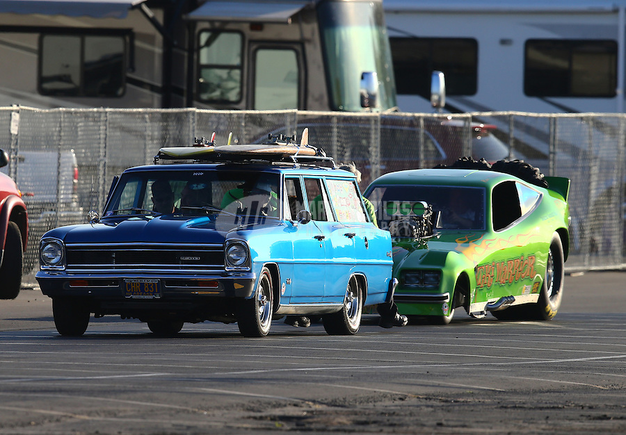 Feb 12, 2016; Pomona, CA, USA; NHRA Ron Huegli in the Tiki Warrior BB funny car is towed back to the pits by a chevrolet station wagon tow vehicle during qualifying for the Winternationals at Auto Club Raceway at Pomona. Mandatory Credit: Mark J. Rebilas-USA TODAY Sports