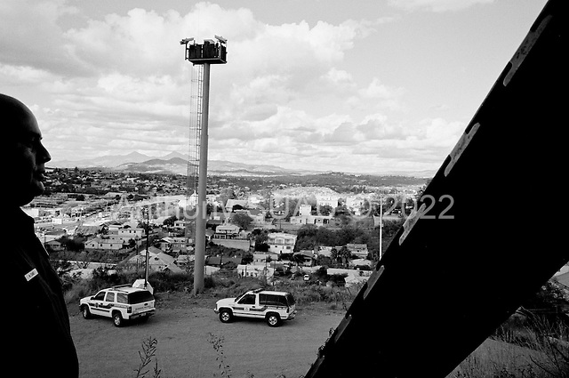 Nogales, Arizona.USA.October 24 2006..The US border patrol watches along the border fence that separates Nogales, Mexico and Nogales USA. The fence extends for several miles in either direction off the port of entry - then there is little to stop people from crossing illegally. Nogales is flooded with Mexicans legal and illegal and is mostly a transit and shopping town.