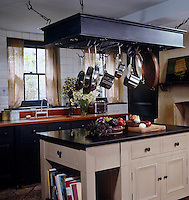 Stainless steel pots hang on meat hooks from a rack above the central kitchen island