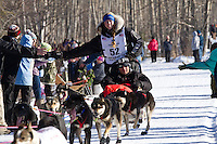 Anna Berington and team run past spectators on the bike/ski trail during the Anchorage ceremonial start during the 2014 Iditarod race.<br /> Photo by Britt Coon/IditarodPhotos.com