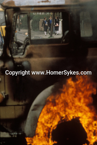 Ireland The Troubles. Belfast schoolgirls walk home after school past hijecked lorry set on hire by oung trouble makers and used as a barricade. Belfast. 1980s