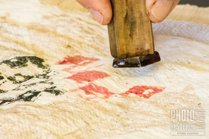 Kapa making on the Big Island: A kapa maker prints designs on kapa with a wooden stamp dipped in native plant dyes.