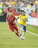 Brazil forward Neymar (10) moves the ball down the sideline as Portugal midfielder Miguel Veloso (4) gives chase.  In an International friendly match Brazil defeated Portugal, 3-1, at Gillette Stadium on Sep 10, 2013.